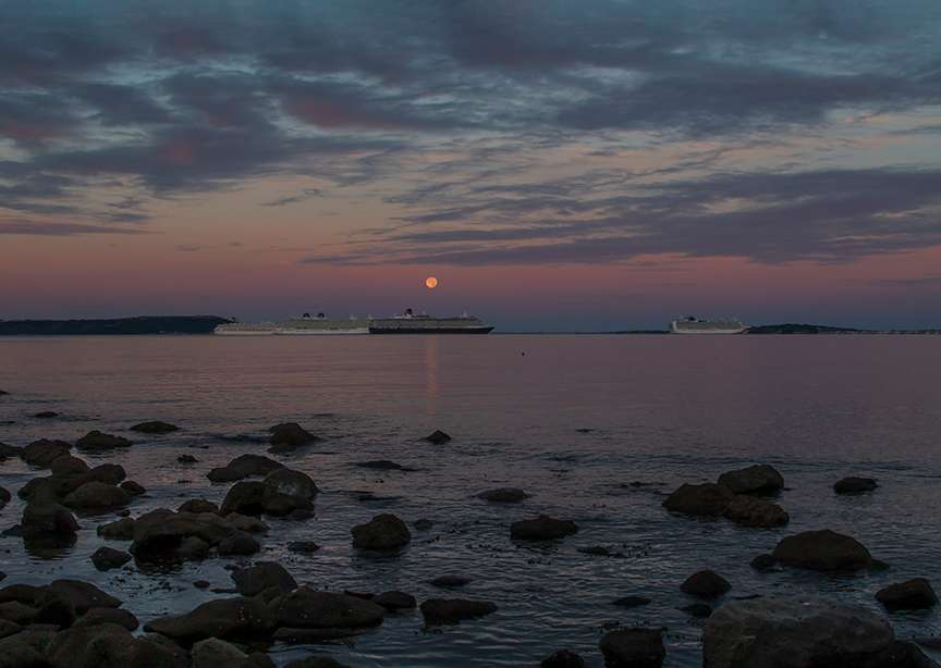 Sturgeon Moonset over Weymouth Bay with mothballed cruise liners. DORCHESTER, Dorset,UK, sent by NMA