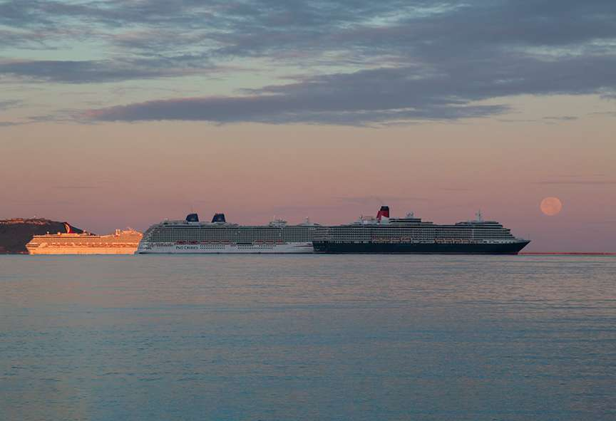 Sunrise and Sturgeon Moonset over Weymouth Bay with mothballed cruise liners. DORCHESTER, Dorset,UK, sent by NMA